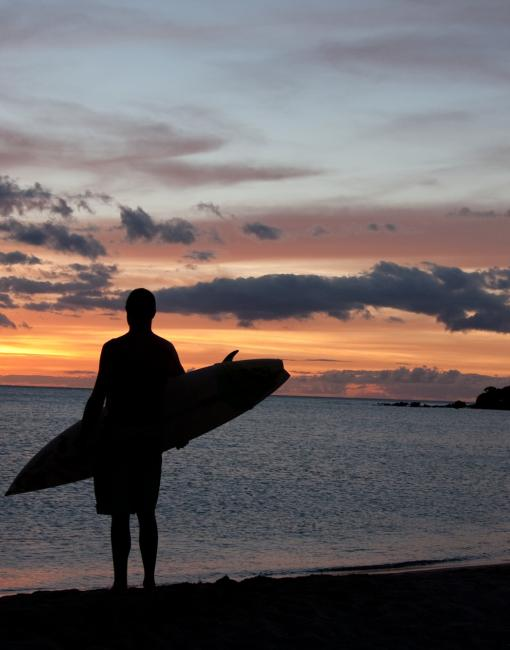 Surfing at sunset on Maui